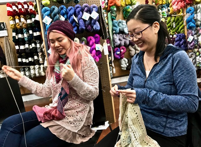 """During an advance Rose City Yarn Crawl event on Feb. 5, 2018, at Twisted yarn shop in Northeast Portland, Marilyn Hynes, right, works on her mystery crochet project, designed by her Seattle friend Noriko Ho, left. Hynes is following one of four """"clues,"""" each a quarter of the pattern downloaded from the website Ravelry.com."""