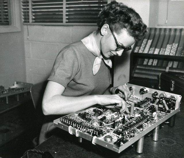 A woman assembles an oscilloscope at Tektronix, ca. 1950s. Many homemakers without job experience were hired and taught a variety of tasks including soldering.