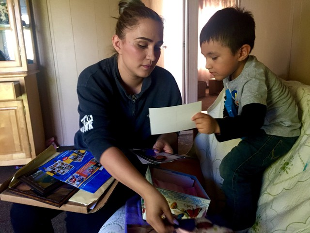 Sally Garcia Acosta shows her son Daniel, 3, photos of his sister. Maria Rosario Perez died from anencephaly, which is affecting three Eastern Washington counties at four times the national average.