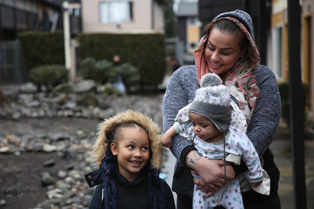 Coya Crispin with her son, Titan, and her daughter, Saraia in the courtyard of Titan Manor. The family recently received a no-fault eviction notice.