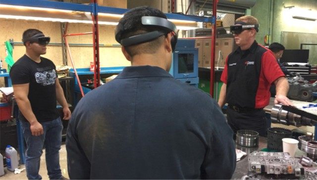 Clackamas Community College automotive instructor Rick Lockwood (right), with his hand on his transmission model, as he and two students go through the hologram transmission animation with Microsoft HoloLenses.
