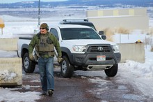 An FBI guard guides a truck out of the compound near the Burns Airport.