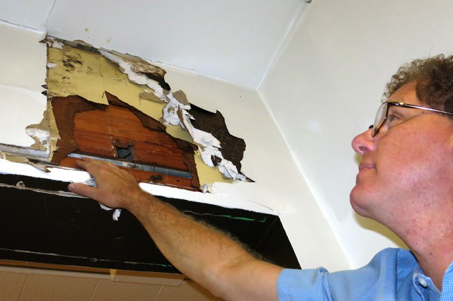 Corbett School District superintendent Randy Trani inspects one of the crumbling walls at the Middle School.