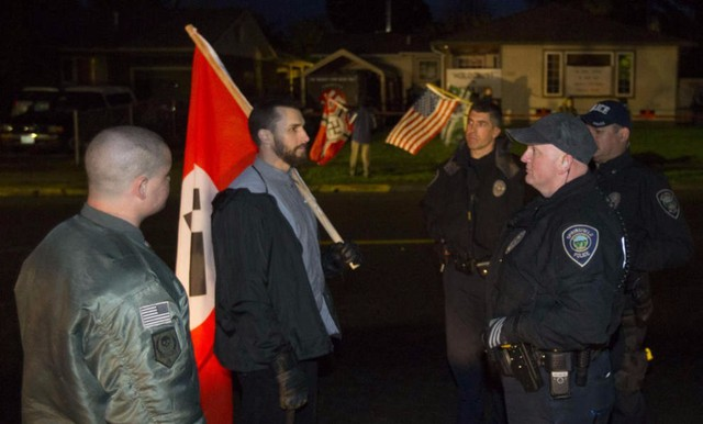 Springfield Police officers separate protestors on G Street in Springfield outside a home displaying Nazi insignias and other slogans after a group of people staged a counter-rally across the street.