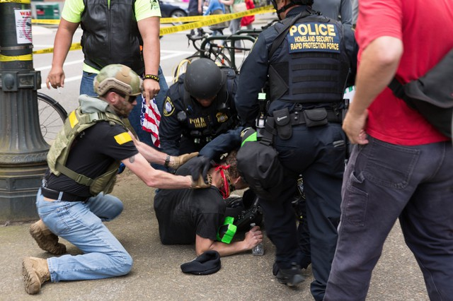 Todd Kelsay, left, assisted federal law enforcement officers in restraining and handcuffing an antifa protester outside of a pro-Trump free speech rally in Portland on Sunday, June 4, 2017. Kelsay's involvement in the arrest has sparked an investigation by the U.S. Attorney's Office.
