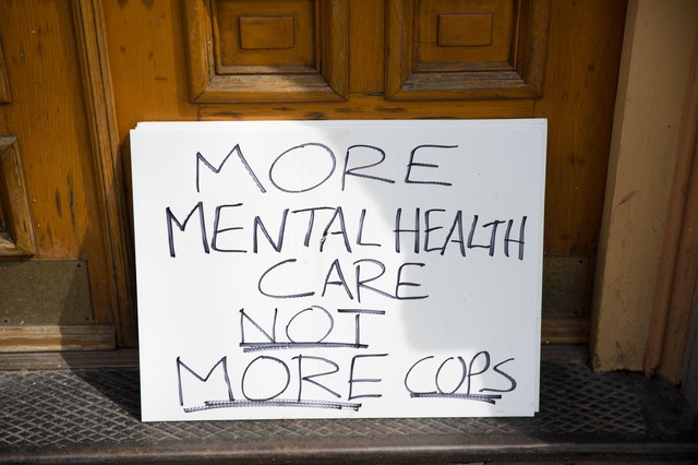 """A sign that sits out the entrance of the Cityteam MinistriesShelter reads """"More Mental Health Not More Cops."""""""