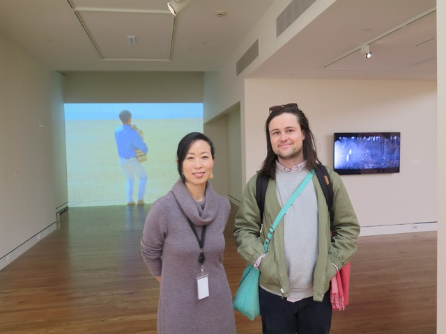 """Grace Kook-Anderson, PAM's Curator of Northwest Art, stands with artist Sam Hamilton in the middle of his exhibition, """"Standard Candles."""""""