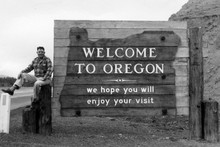 "Dick Sherk next to ""Welcome to Oregon"" sign (1961)"