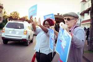 Bernie Sanders fans wave signs outside the new Bernie Sanders campaign headquarters in Portland on April 6, 2016.
