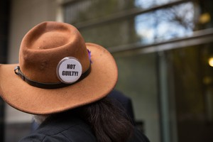 "A supporter displays a ""NOT GUILTY!"" button following the not guilty verdict delivered in the trial of seven occupiers of the Malheur National Wildlife Refuge."