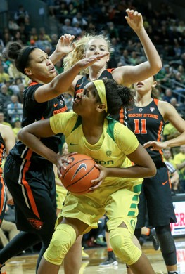 Oregon's Ruthy Hebard (center) is fouled by Oregon State's Breanna Brown (left) during the Ducks 43-40 loss to the Oregon State Beavers at Matthew Knight Arena on Friday. (Collin Andrew/The Register-Guard)
