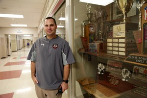 Camas High School Athletic Director Rory Oster in front ofone of several trophy cases honoring the Papermakers.