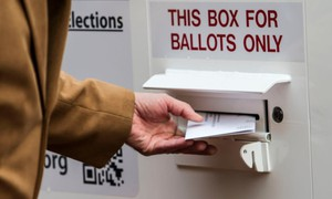A ballot is turned in an official county ballot return box in Oregon.