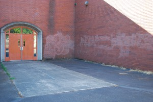 The ghosts of cleaned up graffiti remain on the brick walls of Kellogg.