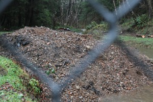 Behind a fence, a recently cleared pile of rock, dirt and twigs sits on the banks of Jetty Creek near the surface water intake for the drinking water plant in Rockway Beach on Oregon's coast. Coastal storms dumped much of this into the creek. Water quality experts say suchstorms make coastal communitiesvulnerable to source water contamination, which they expect to worsen because of climate change.