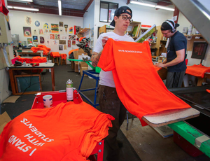 """Production manager Brit Howard screen-prints shirts at Threadbare Print House in Eugene, Ore. with the slogan """"I Stand With Students."""""""