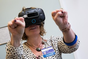Clinic supervisor Mary Hlady collects virtual fireflies in her hands duringa VR for pain management demo at Providence Gresham Rehab and Sports Therapy clinic.