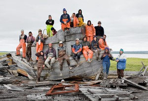 """Corey Arnold's photograph of commercial fishermen from the Graveyard Point fish camp in Bristol Bay, Alaska posing aboard an abandoned """"Monkey Boat"""" near the mouth of the Kvichak River. Arnold is second from left on the bottom."""