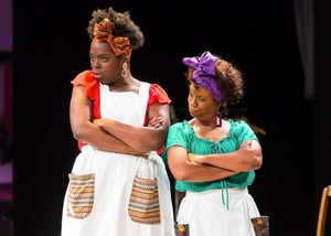 "Playing the roles of two house slaves, Andrea Vernae and Jocelyn Seid enter the stage with protest signs that say ""I don't know what a slave sounded like and neither do you."" Throughout the course of the play, their language switches from modern day vernacular when they're alone to the romanticized vernacular of slaves when they're around white masters."