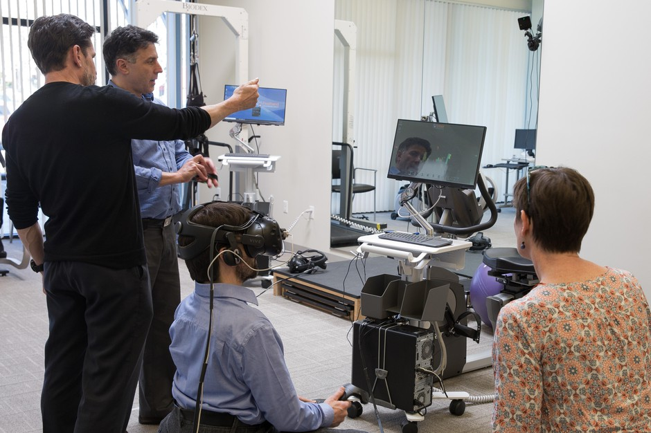 Firsthand Technology CEO Howard Rose (second left)leads a VR for pain management demo at Providence Gresham Rehab and Sports Therapy clinic.